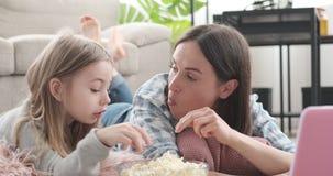 Μητέρα και κόρη που συζητούν τρώγοντας popcorn και προσέχοντας τον κινηματογράφο φιλμ μικρού μήκους