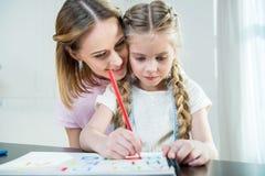 Μητέρα και κόρη που σύρουν τις ζωηρόχρωμες επιστολές στο σπίτι Στοκ Εικόνες