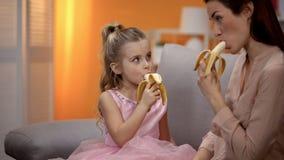 Μητέρα και κόρη που τρώνε τις μπανάνες, υγιής τρόπος ζωής, οργανική διατροφή, διατροφή στοκ εικόνες