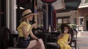 Μητέρα και κόρη που τρώνε το παγωτό στον καφέ οδών στη θερινή ημέρα απόθεμα βίντεο