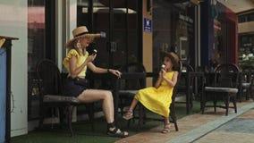 Μητέρα και κόρη που τρώνε το παγωτό στον καφέ οδών στη θερινή ημέρα φιλμ μικρού μήκους