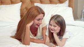 Μητέρα και κόρη που χαμογελούν στη κάμερα, που βρίσκεται στο κρεβάτι από κοινού απόθεμα βίντεο