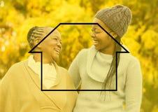 Μητέρα και κόρη που χαμογελούν στο πάρκο με την περίληψη σπιτιών Στοκ φωτογραφία με δικαίωμα ελεύθερης χρήσης