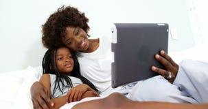 Μητέρα και κόρη που χρησιμοποιούν την ψηφιακή ταμπλέτα στην κρεβατοκάμαρα φιλμ μικρού μήκους