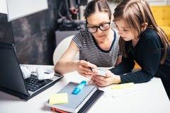 Μητέρα και κόρη που χρησιμοποιούν το έξυπνο τηλέφωνο Στοκ Εικόνα
