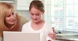 Μητέρα και κόρη που χρησιμοποιούν το lap-top από κοινού απόθεμα βίντεο