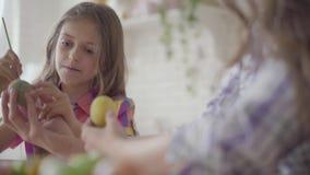 Μητέρα και κόρη που χρωματίζουν τα αυγά Πάσχας με τα χρώματα και τη βούρτσα E r r απόθεμα βίντεο