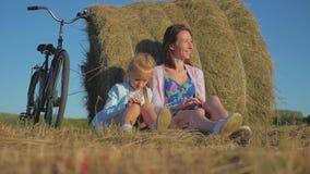 Μητέρα και κόρη σε έναν τομέα με το σωρό σανού σε μια ηλιόλουστη ημέρα Οικογένεια mom με την εύθυμη κόρη ήρθαν με το ποδήλατο μέσ φιλμ μικρού μήκους
