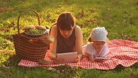 Μητέρα και κόρη σε ένα πικ-νίκ στο ηλιοβασίλεμα απόθεμα βίντεο
