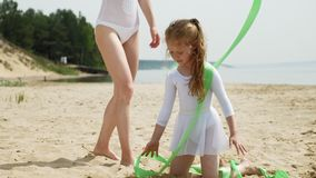 Μητέρα και κόρη στα άσπρα κοστούμια λουσίματος που χορεύουν με τη γυμναστική κορδέλλα σε μια αμμώδη παραλία Καλοκαίρι, αυγή φιλμ μικρού μήκους
