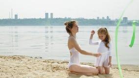 Μητέρα και κόρη στα άσπρα κοστούμια λουσίματος που χορεύουν με τη γυμναστική κορδέλλα σε μια αμμώδη παραλία Καλοκαίρι, αυγή απόθεμα βίντεο