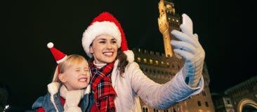 Μητέρα και κόρη στα καπέλα Χριστουγέννων που παίρνουν selfie στη Φλωρεντία Στοκ εικόνα με δικαίωμα ελεύθερης χρήσης