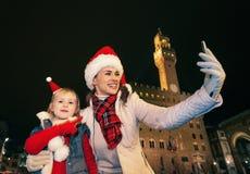 Μητέρα και κόρη στα καπέλα Χριστουγέννων που παίρνουν selfie στη Φλωρεντία Στοκ Εικόνες