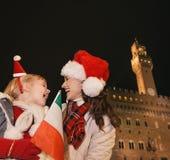 Μητέρα και κόρη στα καπέλα Χριστουγέννων που εξετάζουν η μια την άλλη Στοκ Εικόνες