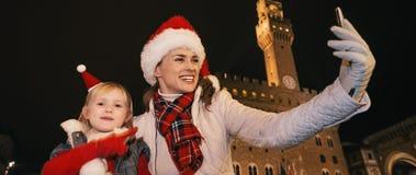 Μητέρα και κόρη στα καπέλα Χριστουγέννων που παίρνουν selfie στη Φλωρεντία Στοκ φωτογραφία με δικαίωμα ελεύθερης χρήσης