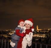 Μητέρα και κόρη στα καπέλα Χριστουγέννων που παρουσιάζουν αντίχειρες, Ιταλία Στοκ Φωτογραφία
