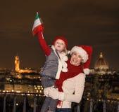 Μητέρα και κόρη στα καπέλα Χριστουγέννων στη σημαία αύξησης της Φλωρεντίας Στοκ φωτογραφία με δικαίωμα ελεύθερης χρήσης