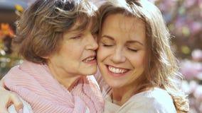 Μητέρα και κόρη, στενό πορτρέτο άνοιξη στον ανθίζοντας κήπο Οι γυναίκες γελούν, αγκαλιάζουν και φιλούν η μια την άλλη φιλμ μικρού μήκους