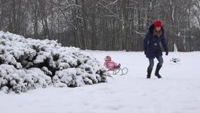 Μητέρα και μικρό κορίτσι που έχουν τη διασκέδαση στο έλκηθρο σε ένα χειμερινό πάρκο 4K απόθεμα βίντεο