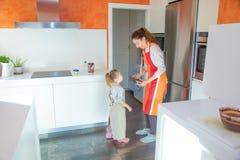 Μητέρα και μικρό κορίτσι στην κουζίνα που παίρνει μια φόρμα για να μαγειρεψει ένα ασβέστιο στοκ φωτογραφίες