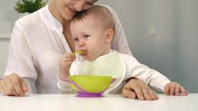 Μητέρα και μωρό με το κύπελλο και το κουτάλι απόθεμα βίντεο