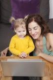 Μητέρα και μωρό που χαμογελούν με τον υπολογιστή Στοκ εικόνα με δικαίωμα ελεύθερης χρήσης