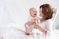 Μητέρα και μωρό στην άσπρη κρεβατοκάμαρα Στοκ φωτογραφία με δικαίωμα ελεύθερης χρήσης