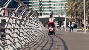 Μητέρα και μωρό στον περιπατητή που περπατά στη μαρίνα του Ντουμπάι απόθεμα βίντεο