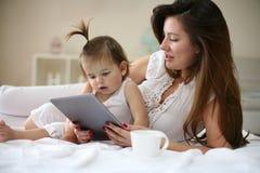 Μητέρα και μωρό στο κρεβάτι Μητέρα και μωρό που χρησιμοποιούν την ψηφιακή ταμπλέτα Στοκ Εικόνες