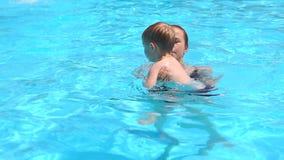Μητέρα και ο γιος της που έχουν τη διασκέδαση σε μια πισίνα απόθεμα βίντεο