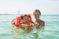 Μητέρα και ο γιος της που παίζουν και που τρέχουν στην παραλία Έννοια της φιλικής οικογένειας Στοκ Φωτογραφία
