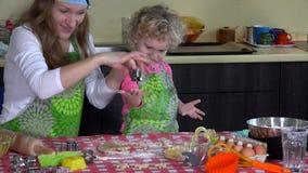 Μητέρα και παιδί που αποκόπτουν τα μπισκότα Χριστουγέννων από την κουζίνα ζύμης στο σπίτι απόθεμα βίντεο
