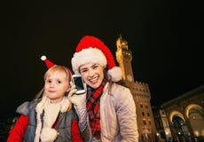 Μητέρα και παιδί στα καπέλα Χριστουγέννων που μιλούν στο τηλέφωνο κυττάρων Στοκ εικόνες με δικαίωμα ελεύθερης χρήσης