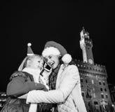 Μητέρα και παιδί στα καπέλα Χριστουγέννων που μιλούν στο smartphone, Ιταλία Στοκ Εικόνες