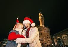 Μητέρα και παιδί στα καπέλα Χριστουγέννων που μιλούν στο smartphone, Ιταλία Στοκ Φωτογραφίες
