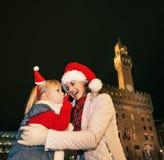 Μητέρα και παιδί στα καπέλα Χριστουγέννων στη Φλωρεντία με κινητό Στοκ Εικόνες