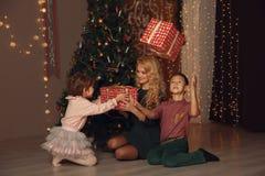 Μητέρα και παιδιά που ανταλλάσσουν και που ανοίγουν τα χριστουγεννιάτικα δώρα Στοκ Εικόνες
