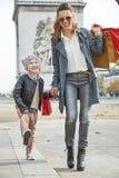 Μητέρα και παιδί με τις τσάντες αγορών στο Παρίσι που πηγαίνει προς τα εμπρός Στοκ εικόνα με δικαίωμα ελεύθερης χρήσης