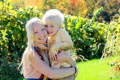 Μητέρα και παιδί που αγκαλιάζουν στον οπωρώνα της Apple φθινοπώρου Στοκ εικόνα με δικαίωμα ελεύθερης χρήσης