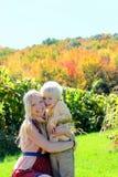 Μητέρα και παιδί που αγκαλιάζουν στον οπωρώνα της Apple φθινοπώρου Στοκ Φωτογραφίες