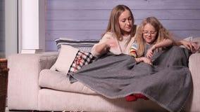 Μητέρα και παιδί που θερμαίνουν κάτω από το κάλυμμα στο σπίτι απόθεμα βίντεο