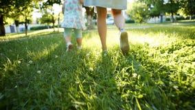 Μητέρα και παιδί που περπατούν στη χλόη φιλμ μικρού μήκους