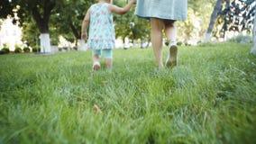 Μητέρα και παιδί που περπατούν στη χλόη απόθεμα βίντεο