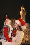 Μητέρα και παιδί στα καπέλα Χριστουγέννων που εξετάζουν το ένα το άλλο, Ιταλία Στοκ Εικόνα