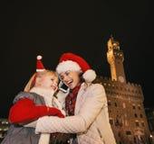 Μητέρα και παιδί στα καπέλα Χριστουγέννων που μιλούν στο smartphone, Ιταλία Στοκ Εικόνα