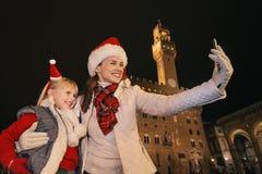 Μητέρα και παιδί στα καπέλα Χριστουγέννων που παίρνουν selfie στη Φλωρεντία Στοκ εικόνα με δικαίωμα ελεύθερης χρήσης