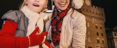 Μητέρα και παιδί στα καπέλα Χριστουγέννων σε χρησιμοποίηση της Φλωρεντίας κινητή Στοκ Φωτογραφίες