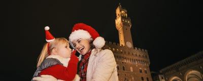 Μητέρα και παιδί στα καπέλα Χριστουγέννων στη Φλωρεντία που μιλά σε κινητό Στοκ Φωτογραφία