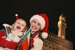 Μητέρα και παιδί στα καπέλα Χριστουγέννων στη Φλωρεντία που παρουσιάζει σημαία Στοκ φωτογραφίες με δικαίωμα ελεύθερης χρήσης