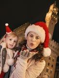 Μητέρα και παιδί στα καπέλα Χριστουγέννων στο φυσώντας φιλί αέρα της Φλωρεντίας Στοκ εικόνες με δικαίωμα ελεύθερης χρήσης